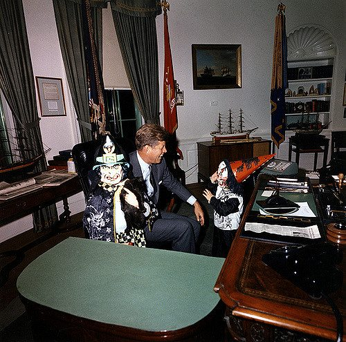 ST-C372-6-63 31 October 1963 Halloween visitors with the President. President Kennedy, John F. Kennedy Jr., Caroline Kennedy. White House, Oval Office. Photograph by Cecil Stoughton, White House, in the John F. Kennedy Presidential Library and Museum, Boston.